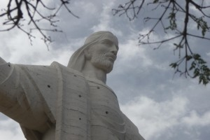 A statue of Jesus Christ stand on a high hill overlooking Cochabamba below.